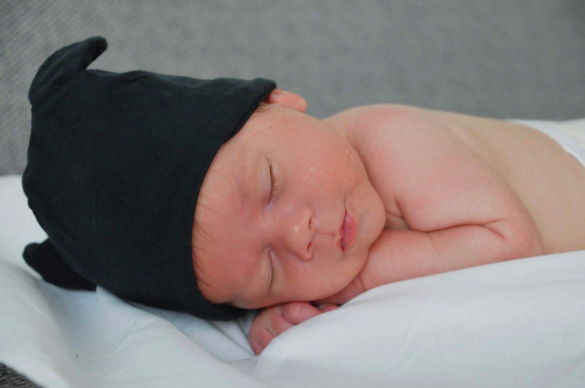neonato mentre dorme con cappello nero